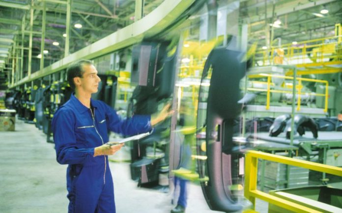 Man inspecting auto parts on assembly line