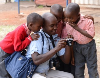 Justus looking at photos with the children near Kibera Paper