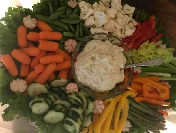 cucumber, carrots, cauliflower, snap peas, peppers and asparagus on a pretty vegetable tray with dip in the center and garnished with lettuce