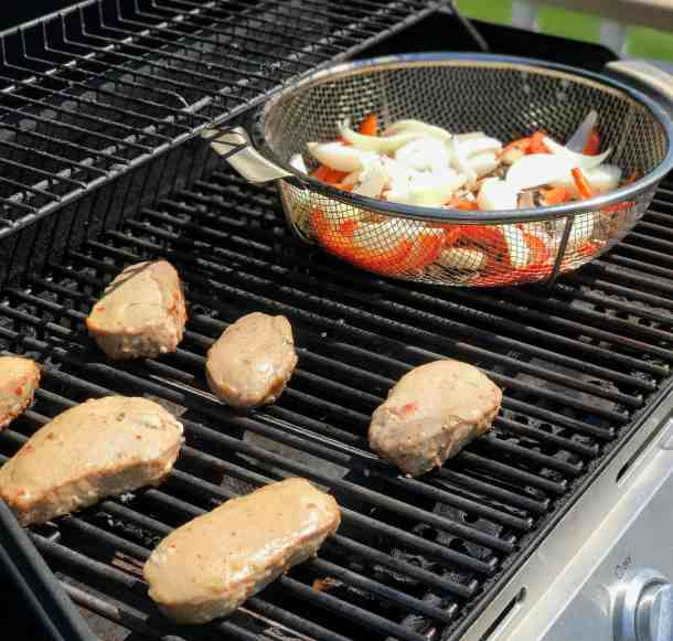 Italian marinated pork chops on a gas grill with a grill basket of vegetables