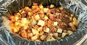 Slow cooker of red potato cubes loaded with bacon and cheese