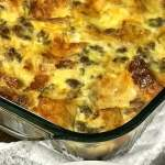 Corner of baked sausage, egg and cheese casserole in dish