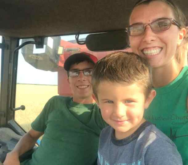 Courtney Nelson in tractor with grain cart harvesting wheat