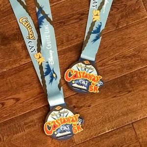 Castaway Cay 5K medals on a wood floor