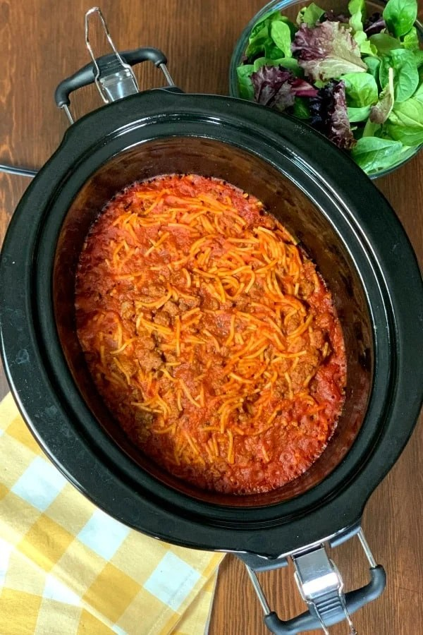 Yellow plaid napkins, Farmhouse Crock Pot Spaghetti in crock pot and bowl of salad