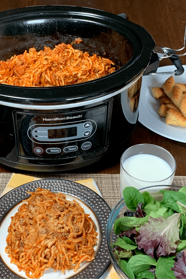 Plate Crock Pot Spaghetti next to crock pot, salad, glass of milk & breadsticks