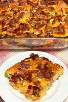 Square piece of bacon, egg and cheese Breakfast Casserole next to a full casserole dish on a red plaid napkin