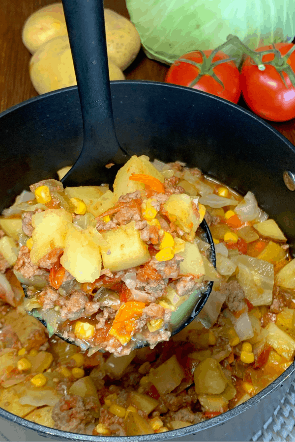 spoonful of Beefy Garden Soup in a dutch oven
