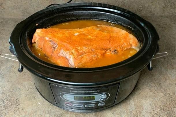 Pork shoulder in crock pot covered in lowrey's seasoned salt