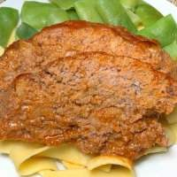 2 slices of applesauce meatloaf on noodles next to Italian green beans