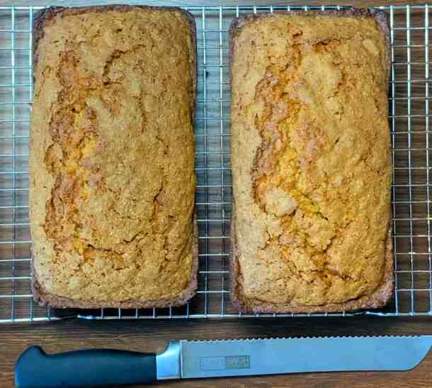 two loaves of carrot bread on cooling rack next to bread knife