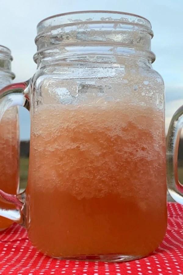 Mason jar of pink slush punch on a red napkin