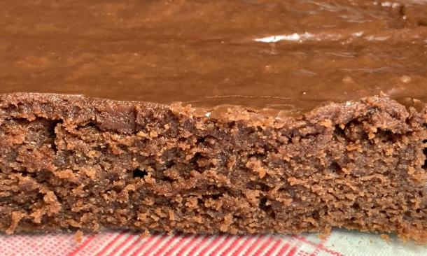 9 x 13 pan of homemade chocolate syrup brownies with chocolate icing on red plaid napkin