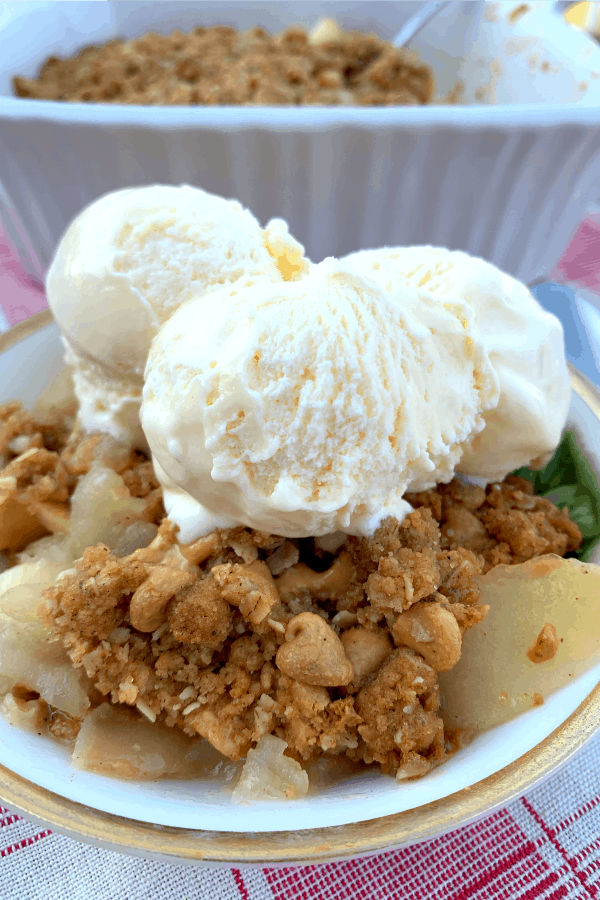peanut butter apple crisp in a dish with scoops of vanilla ice cream on top