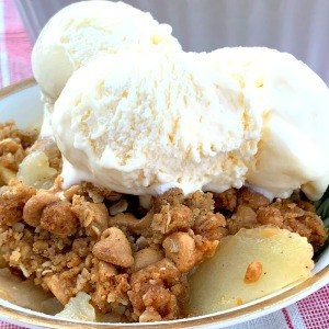 Vanilla ice cream on a dish of peanut butter crumble apple crisp