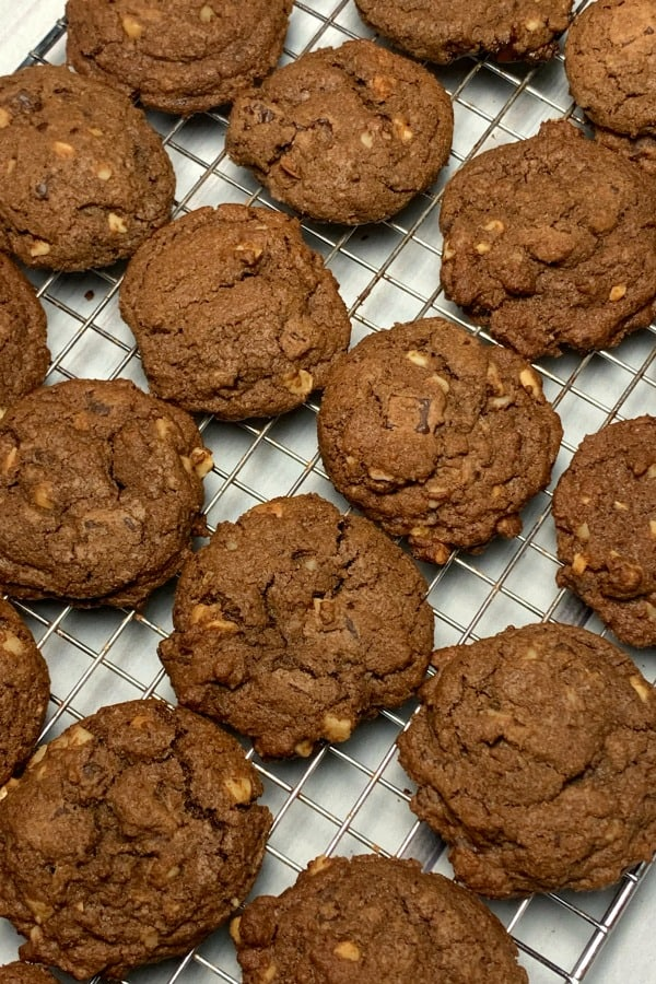 chocolate cookies with chocolate chips and macadamia nuts on a cooling rack