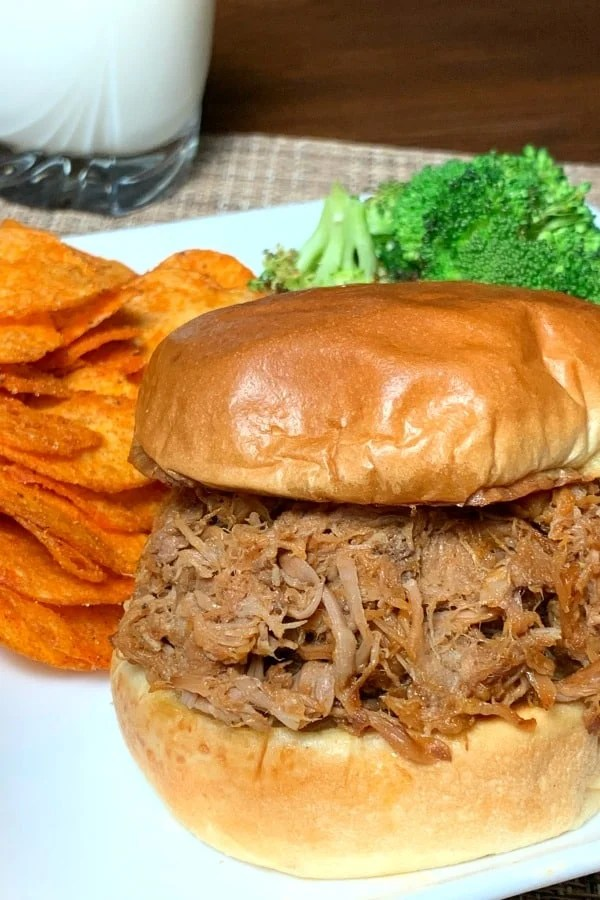 Pulled Pork Sandwich on white plate with potato chips, broccoli and glass of milk