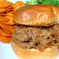 Homemade BBQ Pulled Pork Sandwich on white plate by BBQ potato chips and broccoli