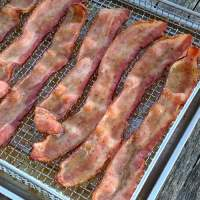 Air fryer candied bacon covered in brown sugar and pepper
