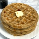 Stack of oatmeal waffles with a pat of butter and maple syrup