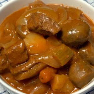 White bowl of hearty beef and vegetable stew