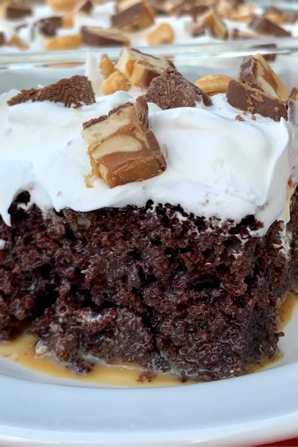 Close up of caramel soaked Snickers Poke Cake with whipped topping