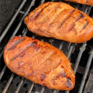 Two chicken breasts marinated in meat marinade on a gas grill