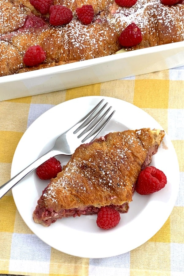 Piece of raspberry cream cheese croissant bake on a white plate with fresh raspberries next to pan