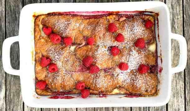 White 9x13 pan of raspberry croissant bake with powdered sugar and fresh raspberries