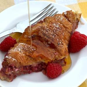 Cream cheese croissant with raspberries and maple syrup on white plate