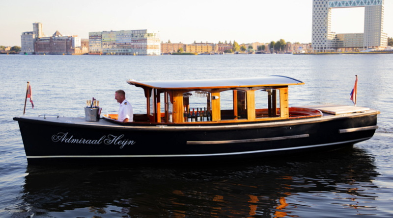 An elegant wooden boat with a canopy with drinks set out on a bar