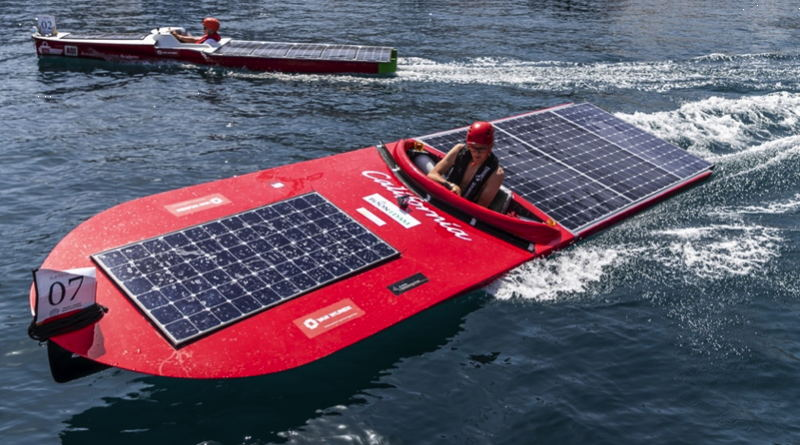 a university student is piloting a solar boat with solar panels on the bow