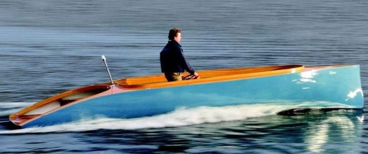 a wooden 1930s style boat painted robins egg blue goes through the water