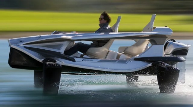 a man drives an open sided jetboat with hydrofoils that keep it flying above the water