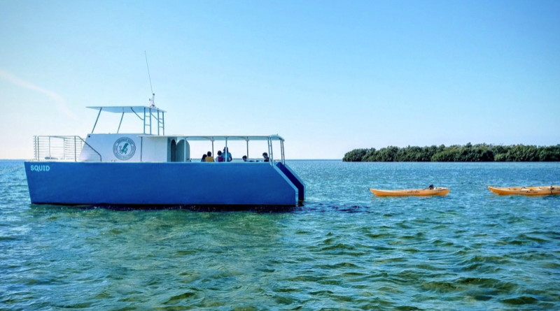 A large catamaran in the Florida Keys water trailed by two kayaks