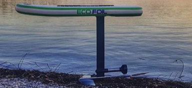 An electric hydrofoil board is standing beside the water