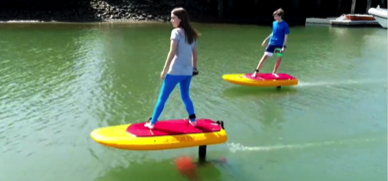A teenage girl and boy ride brightly coloured electric hydrofoils