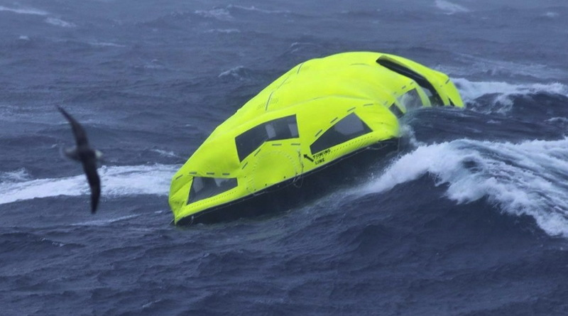 A yellow covered lifeboat is alone in rough waters
