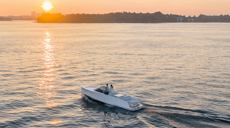 An electric yacht is on a lake at sunset
