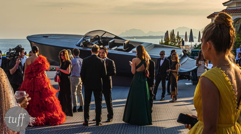 Guests at an elegant AIDS research cocktail party at Cannes gather around a beautiful 10m electric yacht up for auction