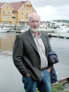 An older gentleman stands in front of a harbour