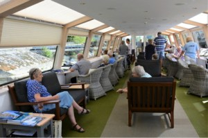 people are seated on comfortable seats chatting and looking out the windows of the observation lounge boat