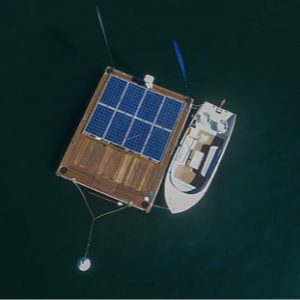 A mooring float dock and sailboat seen from above. The dock has solar panels inlaid in the surface