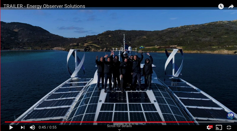 The crew of a 30m boat with the deck covered in solar panels are standing on the deck waving to the camera