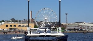 the Energy Observer ship with its rigid wingsails sits in front of the Helsinki SkyWheel
