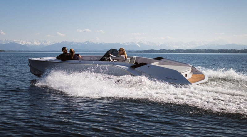 a beautiful electric yacht speeds across an Italian mountain lake