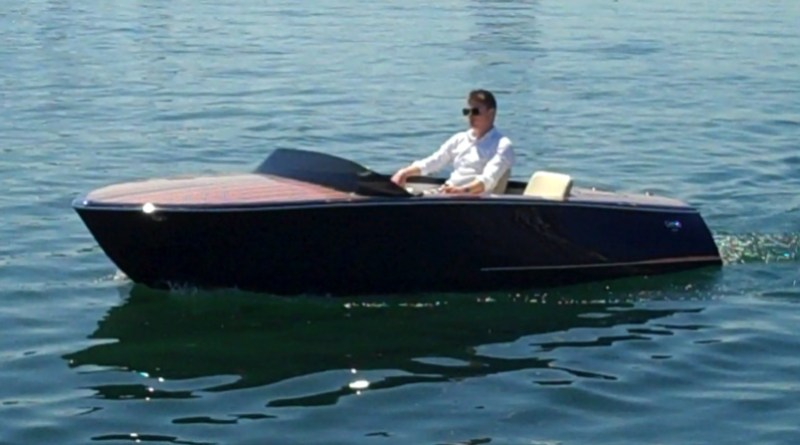 A man is driving a low slung electric boat