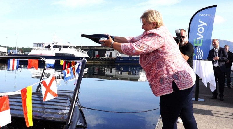 The female Prime Minister of Norway pours a bottle of champagne over the bow of a boat