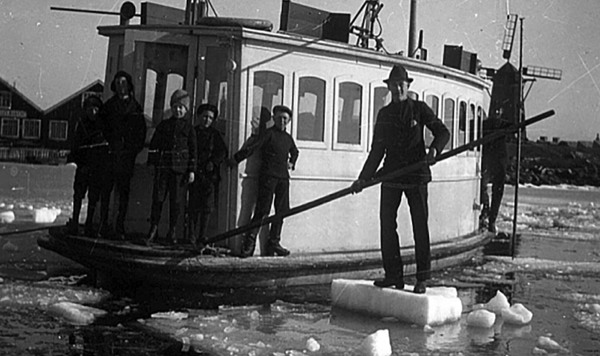 In a photo from 1903 a man is standing on a block of ice in a harbour with an electric ferry in the background