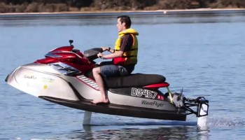 Man riding an electric jetski looking like he is flying above the water
